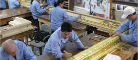 Craftsman carefully gilding the huge frame in the studio
